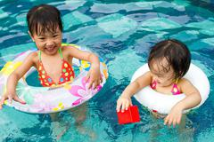 Asian Little Chinese Girls Playing in Swimming Pool - stock photo