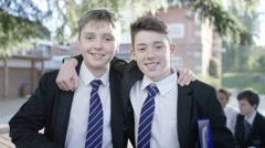 4K Portrait of smiling boys in uniform standing outdoors in school playground Stock Footage