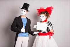 Your text here. Actors mimes holding empty blank board. Colorful studio portrait Stock Photos