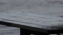 Clear raindrops falling down on wooden table. Sad and rainy weather, bad mood Stock Footage