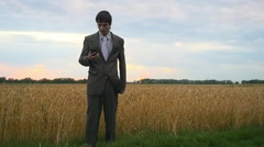 Businessman communicating on mobile phone in wheat field against cloudy sky in - stock footage