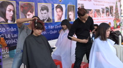 Barbers give free haircuts during a charity event in Saigon, Vietnam Stock Footage