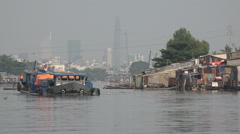Modern Saigon skyline, slum housing, ship sails through canal, Vietnam contrast Stock Footage