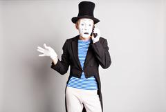 Close-up of a young actor man talking on cell phone at the gray background Stock Photos