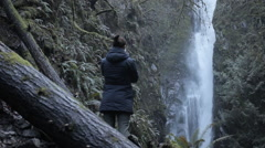 Girl takes a photo of a waterfall in a temperate rain forest - stock footage