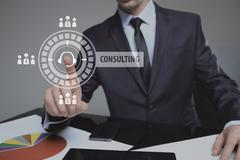 Businessman pressing button on touch screen interface and select Consulting Kuvituskuvat