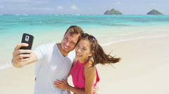Couple on beach vacation taking selfie photo picture with smart phone Stock Footage