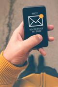 Using mobile smartphone to access e-mail inbox - stock photo
