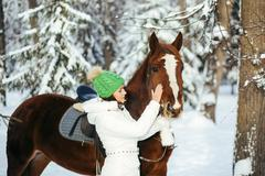 beautiful girl and horse in winter - stock photo
