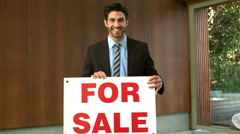 Happy real estate agent with sold sign Stock Footage