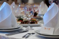 Wine glasses, napkins and salad on the table for the banquet - stock photo