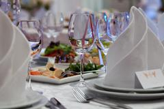 Wine glasses, napkins and salad on the table for the banquet. Stock Photos