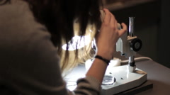 Woman scientist operates microscope Stock Footage