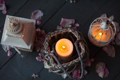 Burning candles in a decorative basket and lantern. Petals of rose on old woo - stock photo