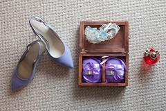 Rings, garter, perfume and shoes - bridal accessories - stock photo