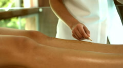 Woman getting her legs waxed by beauty therapist Stock Footage