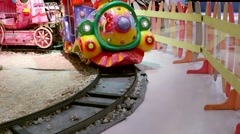 Multicolored glowing fairy-tale cartoon train in the children play center - stock footage