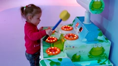 Little girl in a pink jacket with a hammer hits a pop-up toy slot machine Stock Footage