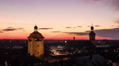 Tower of Berfried and a church tower at sunset in Bruchsal, time lapse Stock Footage