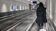 Woman traveling with luggage on moving sidewalk Stock Footage