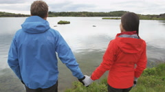Couple holding hands enjoying view of nature lake romantic looking at nature Stock Footage