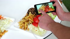 A visitor takes pictures in a cafe with food dish for social networks Stock Footage