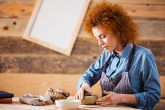 Creative young woman potter making earthen dishes in workshop - stock photo
