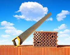 Brick wall with handsaw on bricks Stock Photos