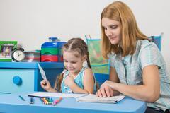 Girl enjoys painting with teacher in kindergarten Stock Photos