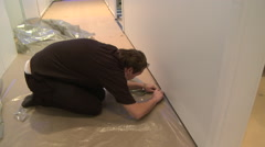 Worker cutting plastic covering the floor Stock Footage