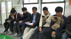 Generation gap, senior man reads papers, young people use smartphones, Korea Stock Footage