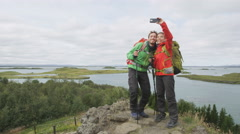 Couple hiking walking and taking phone selfie in nature landscape on Iceland - stock footage