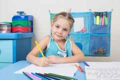 Happy five year old girl draws pencil and looked into the frame - stock photo