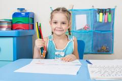 Happy five year old girl picked up a colored pencil and looked into the frame - stock photo