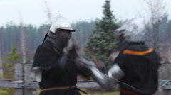 Two strong knights in steel armor hitting each other with swords, slow motion Stock Footage