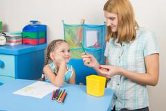 The five-year child looks well if Mom undermined pencil - stock photo