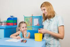 Five-year girl with interest looks like mom sharpens pencils - stock photo