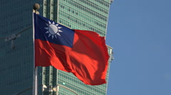 Waving Taiwan national flag, tall Taipei 101 skyscraper tower Stock Footage