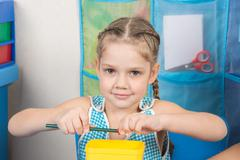 Happy five year old girl sharpens a pencil sharpener small - stock photo