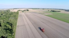 Aerial view of potato harvester on a beautiful landscape with blue skies Stock Footage