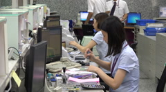 Commercial banking employees help customers at counter desk in Taiwan Stock Footage