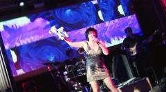 Lolita Milyavskaya perform on stage with plush hare on hand in nightclub Stock Footage