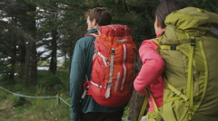 Hiking people walking in forest wearing backpacks - stock footage