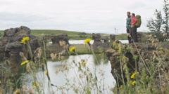 Travel and hiking couple looking at view Iceland on travel holidays vacation - stock footage