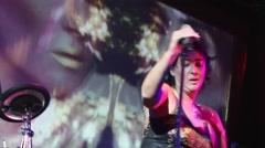 Lolita Milyavskaya perform on stage of nightclub. Raise the microphone stand Stock Footage
