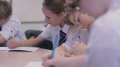 4K Young students working at their desks in school classroom Stock Footage