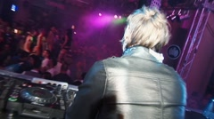 Back side of Dj in leather jaket at turntable in crowded nightclub. Go go girls Stock Footage