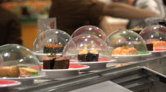 Fresh sushi dishes moving on conveyor belt in Japanese restaurant in Taiwan Stock Footage