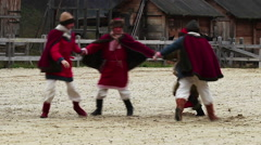 Medieval performance. Cheerful actors are dancing and jumping on the square Stock Footage