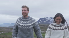 Man and woman looking at view of Iceland nature wearing Icelandic sweaters Stock Footage